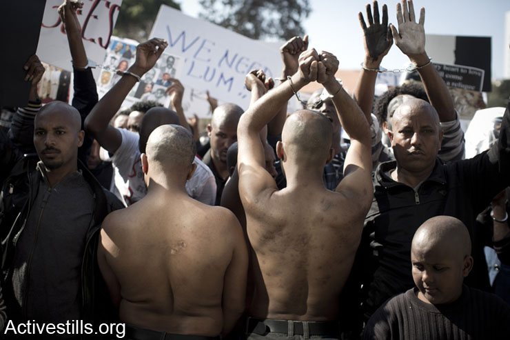 Victims of torture camps in the Sinai Desert, Egypt, show their injuries as African asylum seekers shout slogans during a protest in front of Israel Ministry of Interior offices in Tel Aviv, February 11, 2014. African asylum seekers marched from Levinsky park to protest against the new Holot detention center for African immigrants and called on the Israeli government to recognize their refugee rights. (photo: Activestills.org)