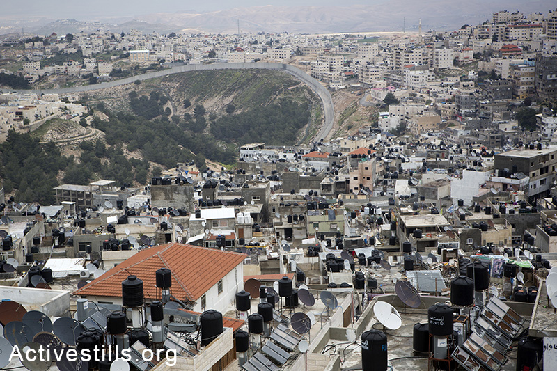 A view over Shua'fat refugee camp and the separation wall that splits the camp from Pisgat Ze'ev (left); on the right Anata and Dahyat A'salam neighbourhoods, March 15, 2014. (Activestills.org)