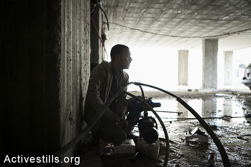 A resident of Ras Shehada plugs the building's pipe to a pump to help the water pressure, East Jerusalem, March 15, 2014. The family of nine, living in the Ras Shehada neighborhood has been going 10 days without running water. (Activestills.org)