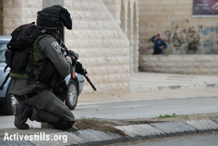 An Israeli soldier prepares to fire rubber-coated steel bullets at stone-throwing Palestinian youth during clashes in the West Bank town of Bethlehem, March 11, 2014. The clashes, which took place in the street near where the Christ at the Checkpoint conference was in its second day, erupted after Israeli forces killed six Palestinians in the West Bank and Gaza in the previous 24 hours. (photo: Ryan Rodrick Beiler/Activestills.org)