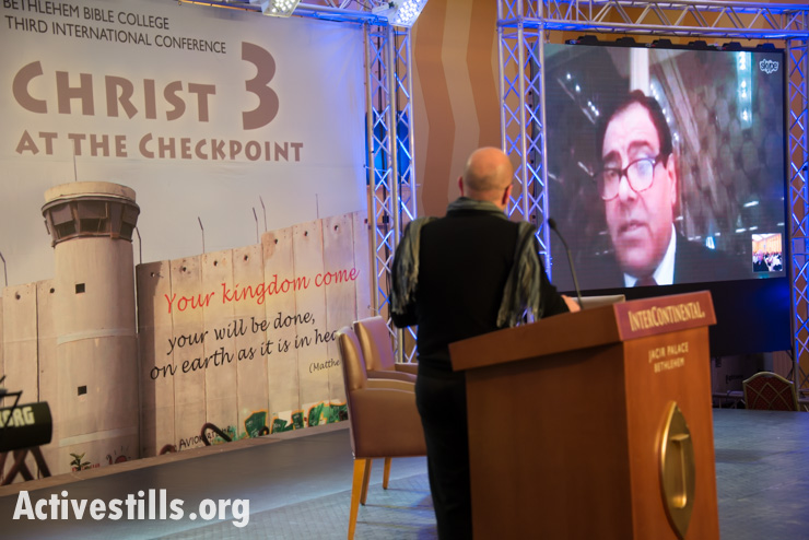 Having been denied entry to Palestine by Israeli authorities, Dr. Izzeldin Abuelaish speaks via Skype to the Christ at the Checkpoint conference taking place in the West Bank town of Bethlehem, March 12, 2014. Abuelaish, who now lives in Canada, lost three daughters, Bessan, Mayar, Aya and their cousin Noor, to Israeli shelling on January 16, 2009 during Operation Cast Lead. (photo: Ryan Rodrick Beiler/Activestills.org)
