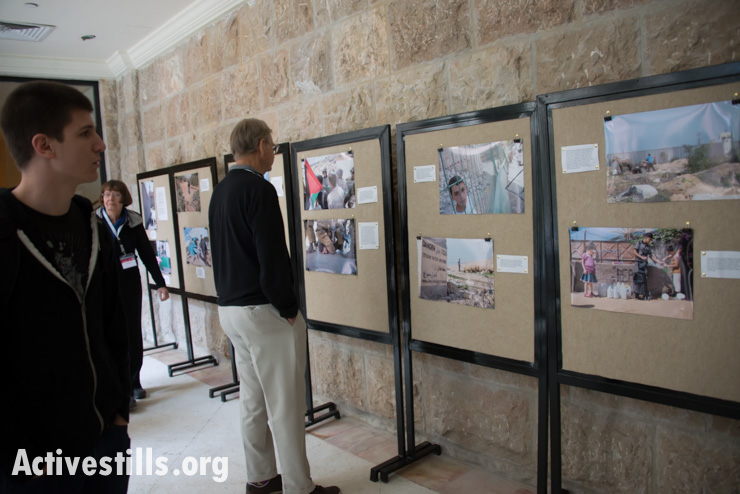 """An exhibition of photographs with the theme """"Life Under Occupation"""" by Activestills photographer Ryan Rodrick Beiler is displayed at the third bi-annual Christ at the Checkpoint Conference in the West Bank town of Bethlehem, March 13, 2014. The third bi-annual Christ at the Checkpoint conference was organized by Palestinian Christians to educate the global church about the reality of injustice faced by those living under occupation and to study how the teachings of Jesus can contribute toward peace and justice advocacy in Palestine and Israel. (photo: Ryan Rodrick Beiler/Activestills.org)"""