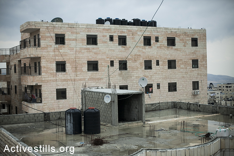 A view over Ras Shehada roof tops, filled with resevre water tanks, East Jerusalem, March 15, 2014. (Activestills.org)