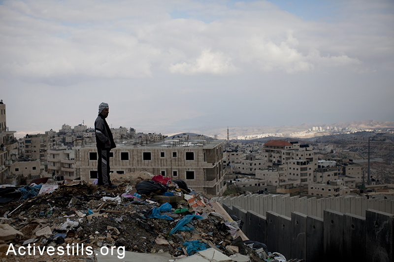 A resident of Ras Shehada over looking the separation wall that cuts the neighbourhood from the rest of the city, East Jerusalem, March 15, 2014. (Activestills.org)