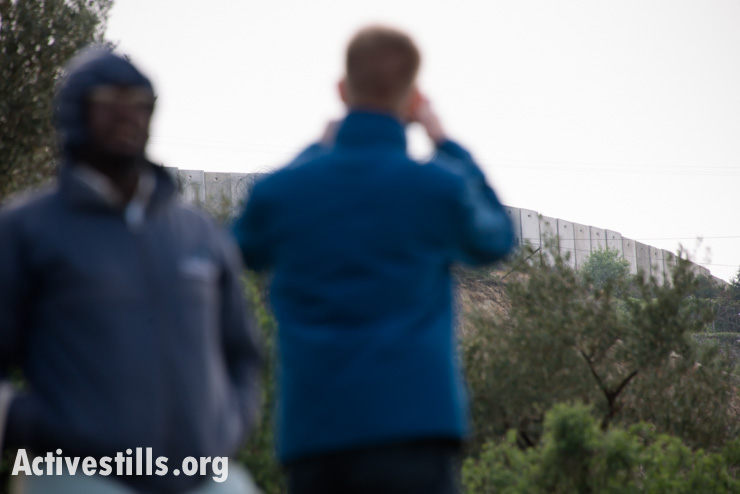 International Christian activists photograph the Israeli separation wall during a field trip organized during the Christ at the Checkpoint conference in the West Bank town of Bethlehem, March 14, 2014. (photo: Ryan Rodrick Beiler/Activestills.org)