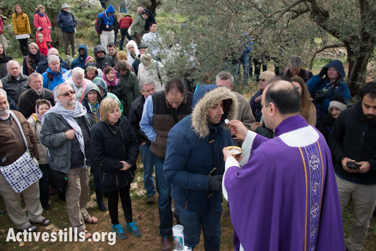 International Christian activists attending the Christ at the Checkpoint conference join Palestinians for a Catholic mass in a West Bank olive grove as a form of nonviolent resistance against the Israeli separation barrier that threatens to further divide land belonging to the town of Beit Jala, March 14, 2014. If built as planned, the wall would separate the Cremisan monastery and a valley of olive groves from the rest of Beit Jala. (photo: Ryan Rodrick Beiler/Activestills.org)