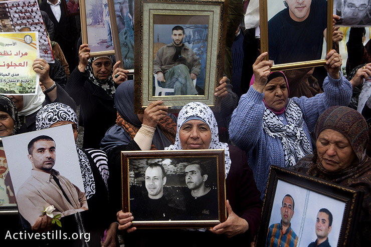 Palestinian women holding framed photos of imprisoned relatives during a rally commemorating Palestinian Prisoners Day, Ramallah, West Bank, April 17, 2013. The 17th of April marks the annual Palestinian Prisoners Day. It was initially set to remind the public of the thousands of Palestinian prisoners that are imprisoned in Israeli jails, where they are routinely exposed to various methods of torture and other forms of inhumane treatment.
