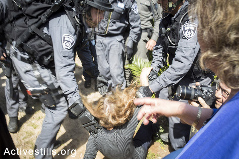 Policemen hold down a protester during the evacuation of the Givat Amal neighborhood. Protesters chanted slogans and burned tires. (photo: Shiraz Grinbaum/Activestills.org)