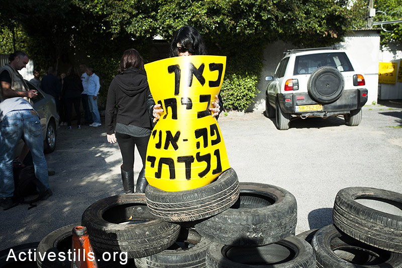 """An activist holds a sign reading """"Here is my home, I was born here,"""" in front of Rivka Chilovsky's house before her eviction, March 27, 2014. (Shiraz Grinbaum/Activestills.org)"""