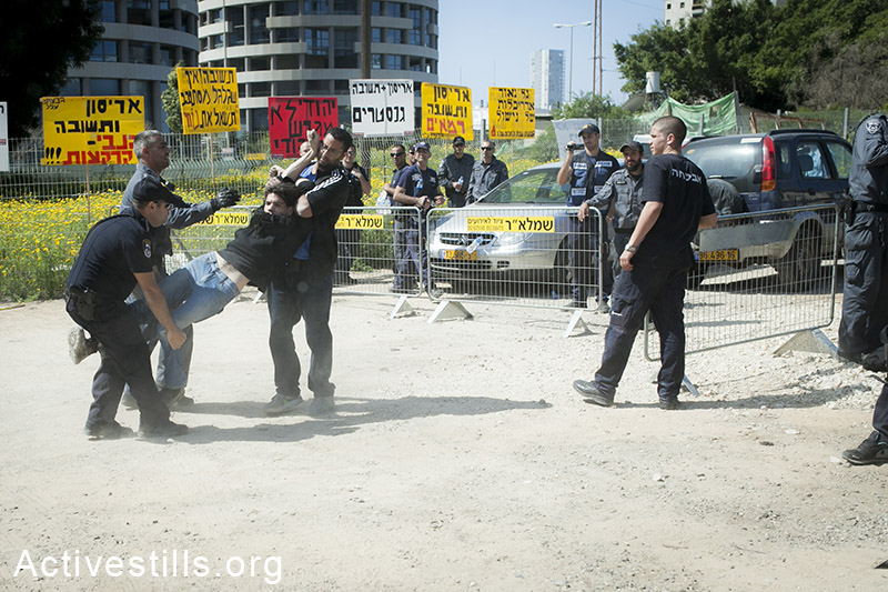 An activists being arrested during a raid of Israeli police and private security forces in Givat Amal neighbourhood,  Tel Aviv, March 27, 2014. (Shiraz Grinbaum/Activestills.org