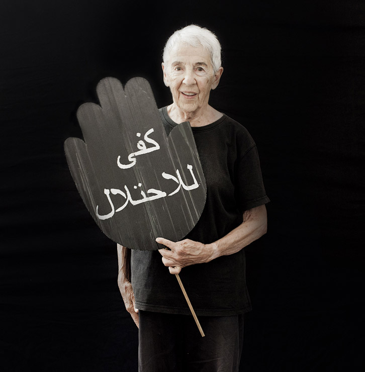 Judy Blanc, 85, co-founder of Women In Black, Jerusalem group, holds a sign that reads 'stop the occupation' in Arabic.