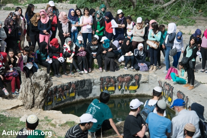 A tour group of Palestinian young women from Sakhnin, Israel, and a group of Jewish boys visit the spring in the depopulated Palestinian village of Lifta, located on the edge of West Jerusalem, Israel, March 4, 2014. During the Nakba, the residents of Lifta fled attacks by Zionist militias beginning in December 1947, resulting in the complete evacuation of the village by February 1948. (Photo by Ryan Rodrick Beiler/Activestills.org)