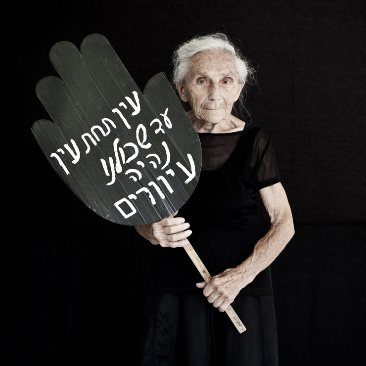 Stela Tzur, 86, co-founder of Women In Black and part of the Haifa group holds a sign that reads 'an eye for an eye until all go blind' in Hebrew.