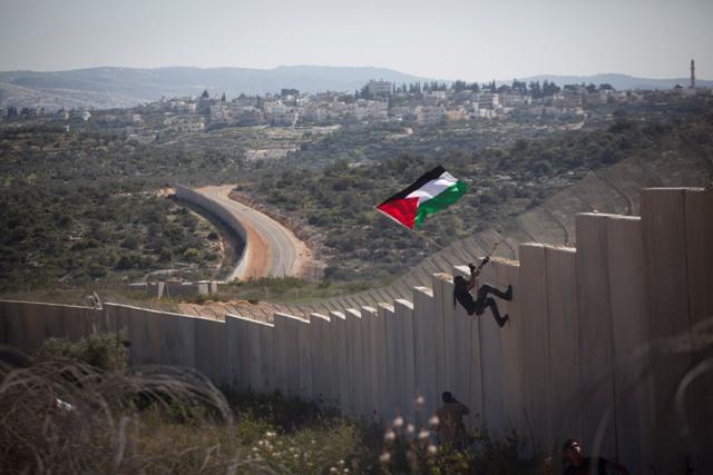 Several Palestinian demonstrators climbed the wall. (Oren Ziv / Activestills)