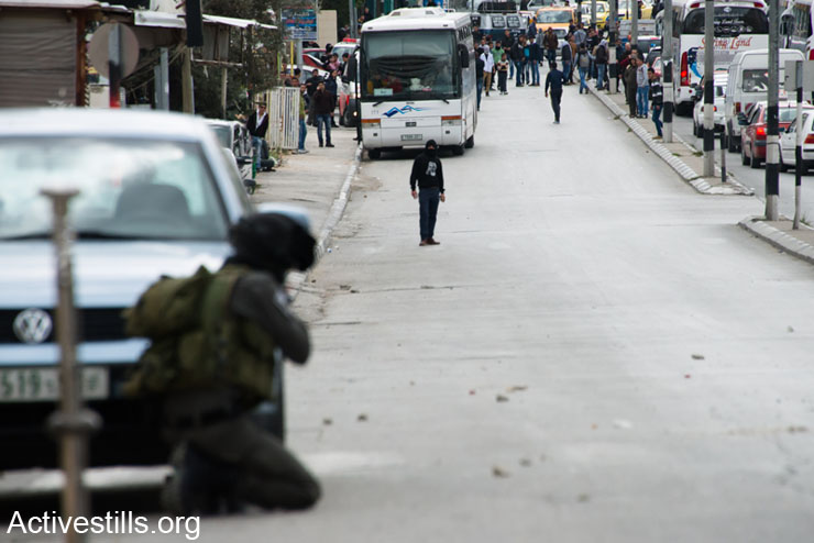 An Israeli soldier prepares to fire rubber-coated steel bullets at stone-throwing Palestinian youth during clashes in the West Bank town of Bethlehem, March 11, 2014. The clashes erupted after Israeli forces killed six Palestinians in the West Bank and Gaza in the previous 24 hours.