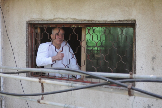 Ismail Shawa standing in the window he is forced to climb through in order to exit and enter his Jaffa home. (Photo by Yudit Ilany)