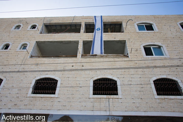 An Israeli flag hangs from the Al Rajabi building, which Israeli settlers want to turn into a new settlement in the Wadi Al Hussein area of Hebron, March 7, 2014. Israeli settlers claim ownership of the building, but the Palestinian owner disputes the sale because it involved a middleman who purchased it under false pretenses. Settlers occupied the Al Rajabi building between March 19, 2007 and December 4, 2008 before being removed due to the court dispute. During this time they violently harassed Palestinian neighbours. When evicted in 2008, the settlers set fire to some Palestinian homesand even shot and injured two men. On September 2, 2013 the Israeli Supreme Court held the final hearing into a dispute regarding ownership of the Al Rajabi building. They have stated that they will issue a final decision in 1-6 months. Until the court's decision is final, the Israeli military will occupy the building.