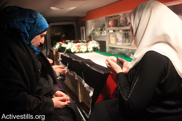 Relatives of Emad Zubaidi, a Palestinian fighter who was Killed in 2001 sit beside his remain inside ambulance, Nablus, West Bank, March 11, 2014.Palestinians received remains of five Palestinian fighters, that were Killed in 2001, 2002 and 2003, from Taibeh checkpoint near the West bank city of Tulkarm.  Israel still holds hundreds of Palestinian bodies in an isolated cemetery in Jordan Valley, West Bank.