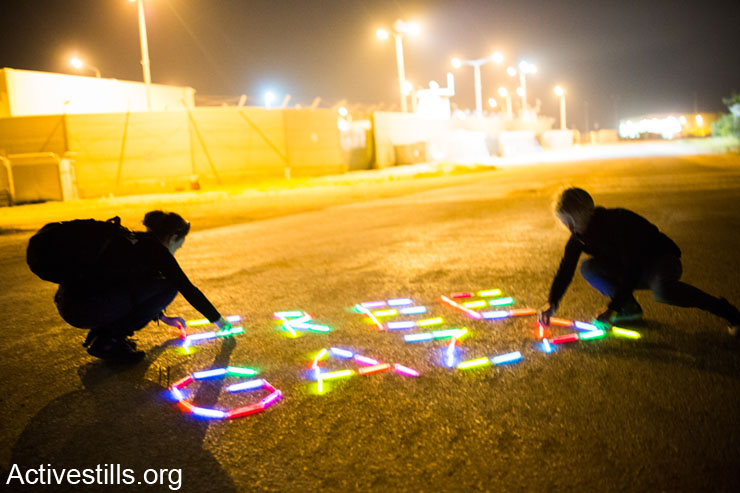 Israeli Women activists form a stick light sign reading Free Gaza in front of Erez crossing , March 8th, 2014. The action is part of a series of direct actions marking IWD.