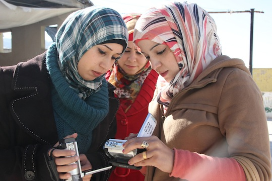 'Atta Najar, Salam Najar and Mi'ad Najar check out the cameras and compare footage in Hebron. (photo: B'Tselem)