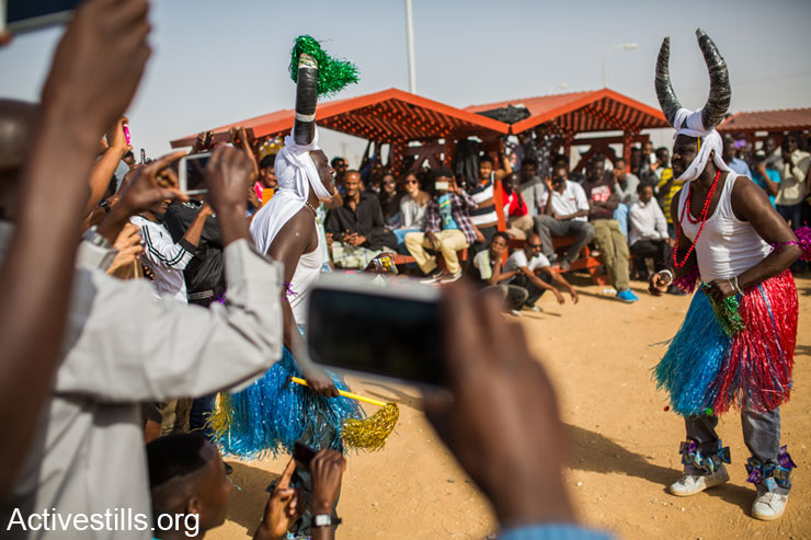 Members of refugee community preform a dance as part of cultural day held in front of Holot open detention center on march 8, 2014. since the opening of the center on December 2013 more then 1000 people wore forced to live in it. testimonies  from the center suggest the the asylum seekers staying in it are living under bad conditions, including shortage in food.