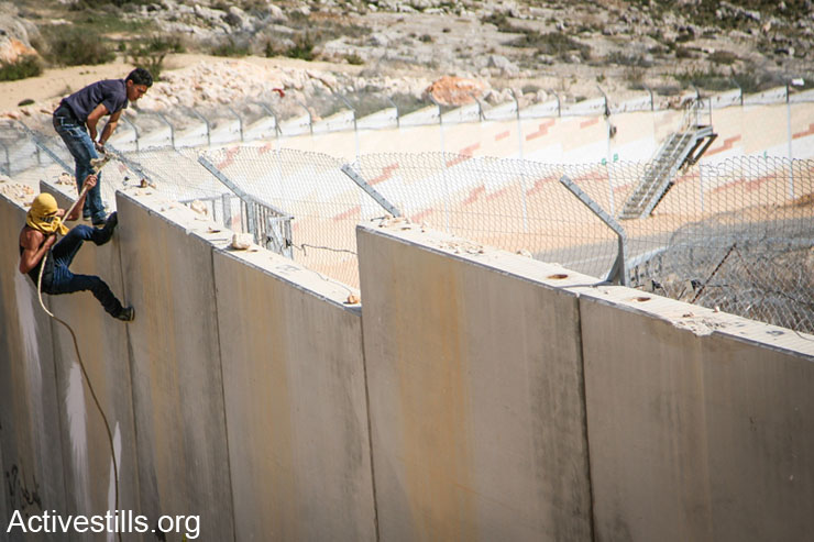 Palestinian youth climb on the Israeli wall during a protest in the West Bank village of Bilin, February 28, 2014.