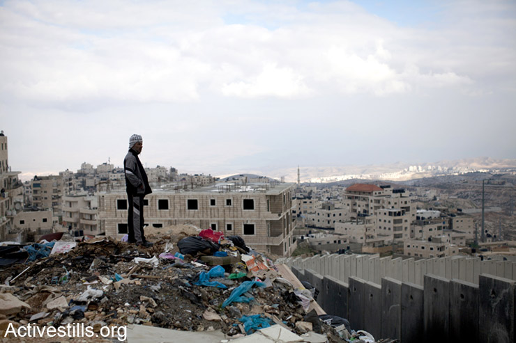 A resident of Ras Shehada neighborhood looks over the separation wall, East Jerusalem, March 15, 2014. (photo: Activestills.org)