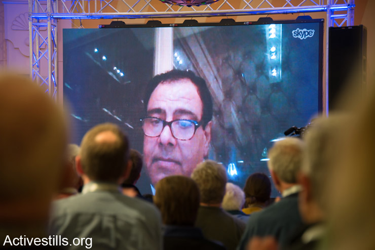 Dr. Izzeldin Abuelaish speaks via Skype to the Christ at the Checkpoint Conference taking place in the West Bank town of Bethlehem because he was denied entry to Palestine by Israeli authorities, March 12, 2014. Dr. Abuelaish, who now lives in Canada, lost three daughters, Bessan, Mayar, Aya and their cousin Noor, to Israeli shelling on January 16, 2009 during Operation Cast Lead. The third bi-annual Christ at the Checkpoint conference was organized by Palestinian Christians to educate the global church about the reality of injustice faced by those living under occupation and to study how the teachings of Jesus can contribute toward peace and justice in Palestine and Israel. (photo: Activestills.org)