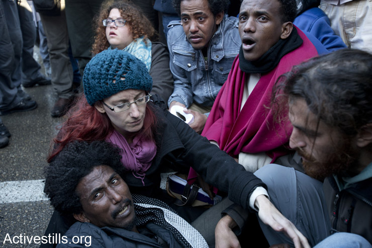 African Asylum seekers and Israeli activists sit on the ground as Israeli immigration officers arrest African asylum seeker during a protest outside the Israeli parliament following a three days March For Freedom, from the South of Israel to Jerusalem, December 17, 2013.