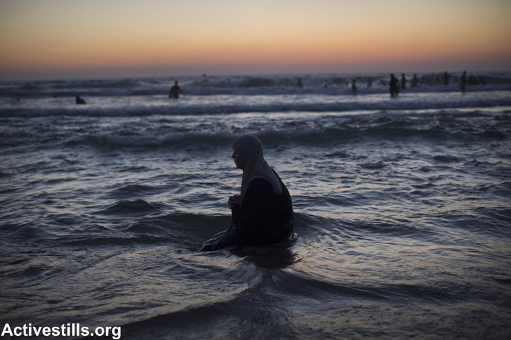 A Palestinian woman prays at the beach during Eid al-Fitr, which marks the end of the holy month of Ramadan, Tel Aviv, Israel, August 8, 2013.