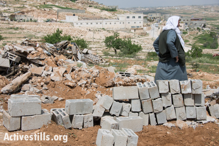 A Palestinian farmer stands near concrete blocks salvaged from the remains of shelters demolished by the Israeli military, Al Tuwani, West Bank, April 2, 2014. Seven shelters built in agricultural areas near the village belonging to different inhabitants of Al Tuwani were demolished on the same morning. (photo: Activestills.org)