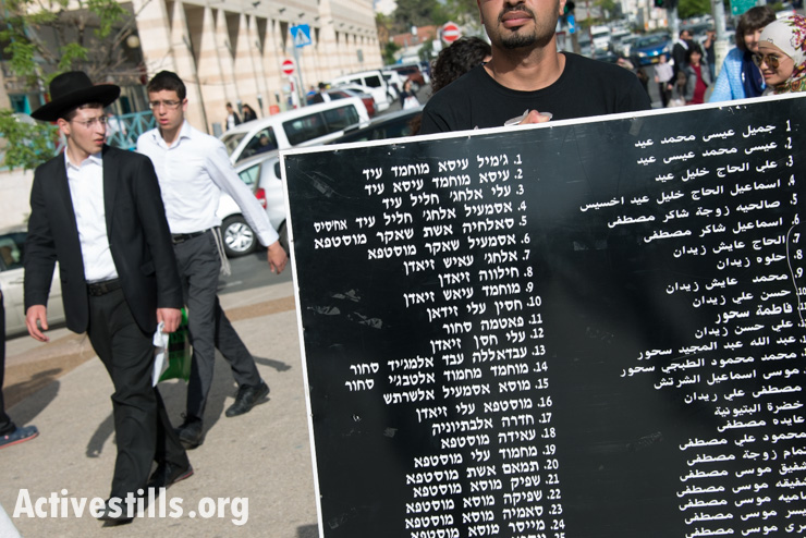 """Israeli Jewish youth watch a procession of Israeli, Palestinian, and international activists carrying names of those who died in the Deir Yassin massacre, Givat Shaul, West Jerusalem, April 10, 2014. On April 9, 1948, some 100-200 Palestinians, including women and children, were killed by the extremist Zionist militias the Irgun and Stern Gang (Lehi) in the village of Deir Yassin. The Israeli activist group Zochrot (""""remembering"""") organizes an annual procession to commemorate those killed and to recount the history of the village. (photo: Activestills.org)"""