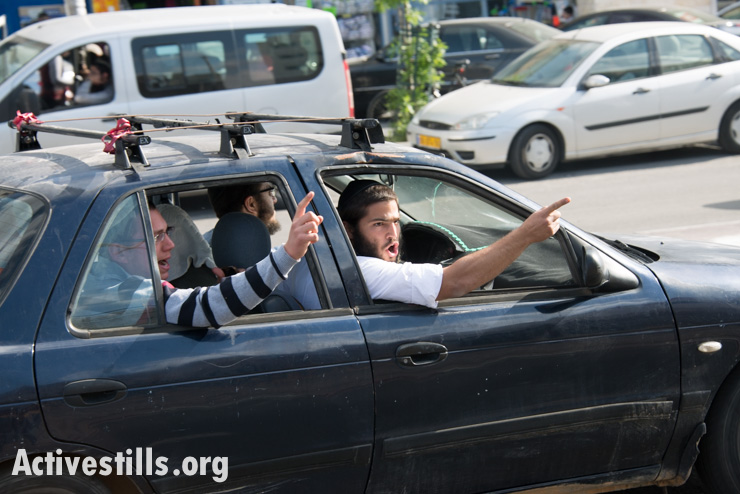 Israelis shout at the procession from a passing car. (photo: Activestills.org)