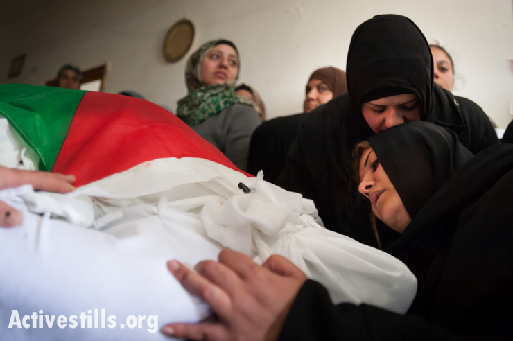 Iman Katamish (right) mourns among family members at the flag-draped body of her mother Noha, Aida Refugee Camp, West Bank, April 15, 2014. Noha Katamish, who had asthma, died from the effects of a tear gas grenade fired into her home by Israeli forces the previous day. She was the mother of one daughter.