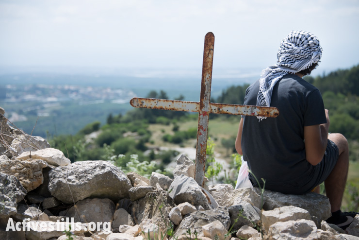 A youth sits near a cross overlooking the surrounding countryside in the displaced Palestinian village of Iqrit in northern Israel, April 21, 2014. Iqrit's original inhabitants were forcibly evacuated in the Nakba of 1948. Though the Israeli high court granted the residents, who are Palestinian citizens of Israel, the right to return to their homes in 1951, the military destroyed the village and has since prevented their return. (photo: Activestills.org)