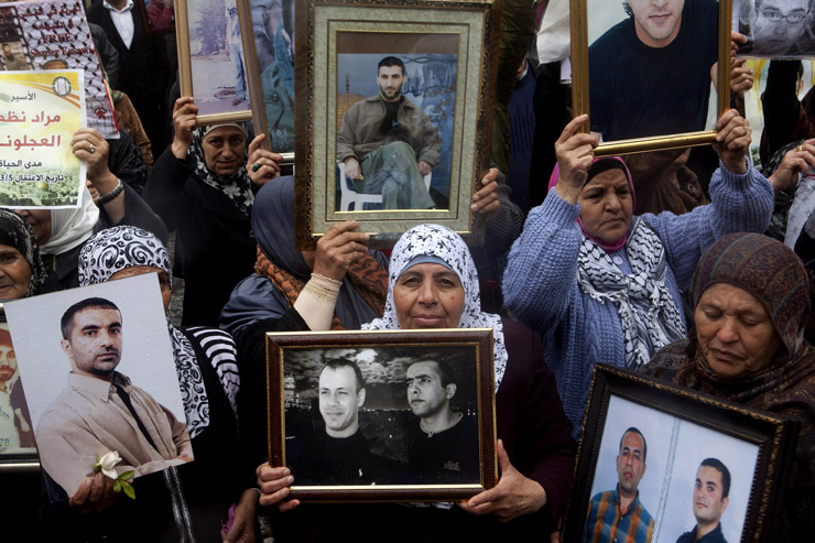 Palestinian women holding framed photos of imprisoned relatives during a rally commemorating the Palestinian Prisoners, Ramallah, West Bank, April 17, 2013. The 17th of April marks the annual Palestinian Prisoners Day. It was initially set to remind the public of the thousands of Palestinian prisoners that are imprisoned in Israeli jails, where they are routinely exposed to various methods of torture and other forms of inhumane treatment.