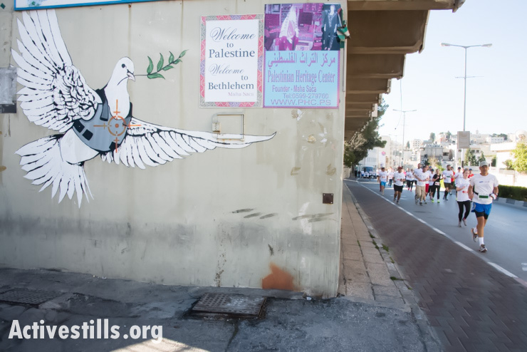 Runners pass a Banksy mural in the West Bank town of Bethlehem during the second annual Palestine Marathon, April 11, 2014. (photo: Activestills.org)