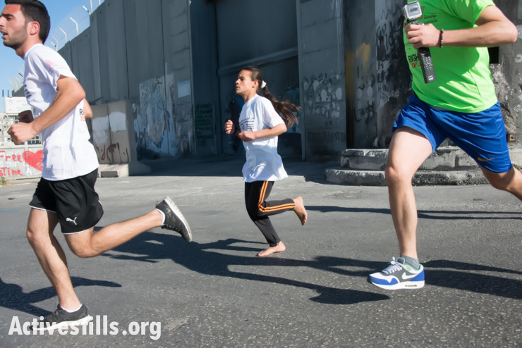 A Bedouin child runs in bare feet near the Israeli separation wall in the second annual Palestine Marathon in the West Bank town of Bethlehem, April 11, 2014. (photo: Activestills.org)