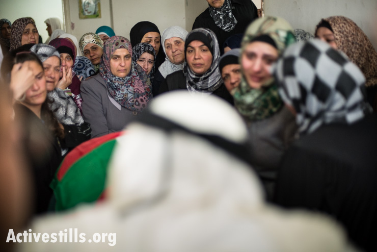 Women mourn as Mohammad Katamish enters the room where the body of his daughter Noha awaits burial, Aida Refugee Camp, West Bank, April 15, 2014. Noha Katamish, who had asthma, died from the effects of a tear gas grenade fired into her home by Israeli forces the previous day. She was the mother of one daughter.