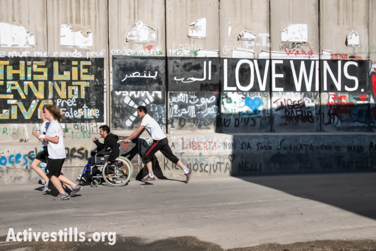 A Palestinian runner pushes a friend in a wheelchair along the Israeli separation wall dividing the West Bank town of Bethlehem during the second annual Palestine Marathon, April 11, 2014. (photo: Activestills.org)