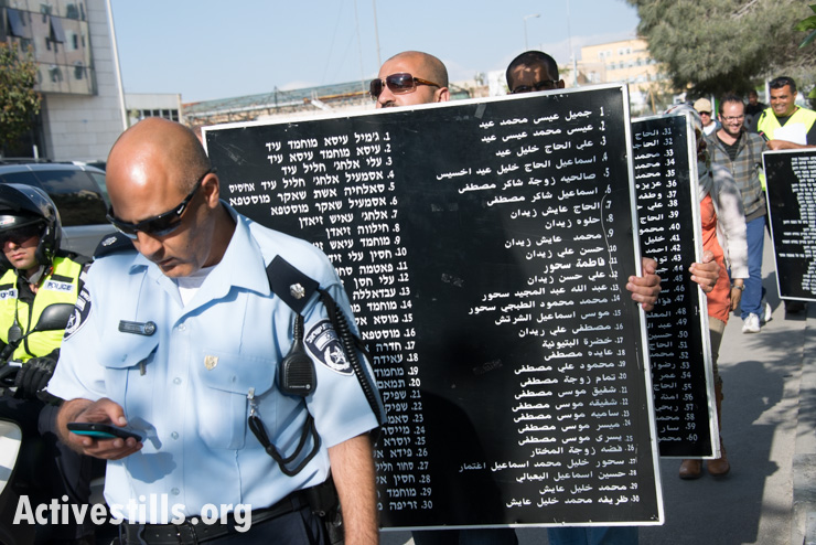 Due to incidents of harassment by right-wing activists in previous years, Israeli police escort the procession of Israeli, Palestinian, and international activists carrying names of those who died in the Deir Yassin massacre. (photo: Activestills.org)