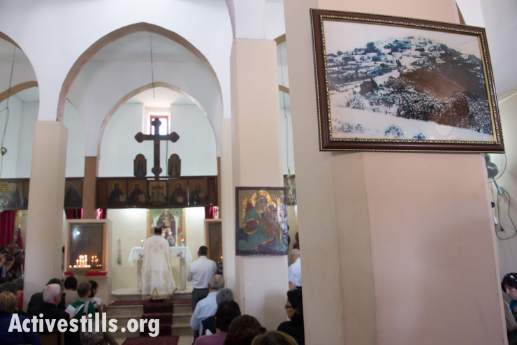 On Easter Monday, a photograph of the Palestinian village of Iqrit before its destruction hangs in the church, the only building to remain. Northern Israel, April 21, 2014. Iqrit's original inhabitants were forcibly evacuated in the Nakba of 1948. Though the Israeli high court granted the residents, who are Palestinian citizens of Israel, the right to return to their homes in 1951, the military destroyed the village and has since prevented their return. Only the village's church and cemetery remained intact, and are still used by village residents while they campaign for a full return.