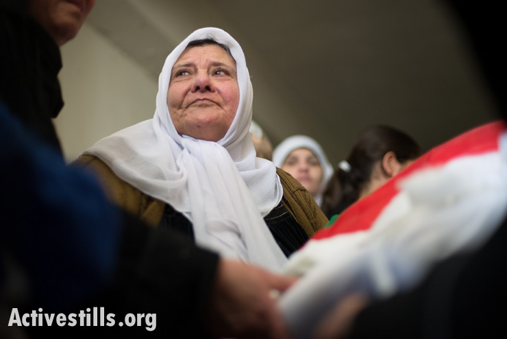 Zahiyya Katamish mourns among family members near the flag-draped body of her daughter Noha, Aida Refugee Camp, West Bank, April 15, 2014. Noha Katamish, who had asthma, died from the effects of a tear gas grenade fired into her home by Israeli forces the previous day. She was the mother of one daughter.