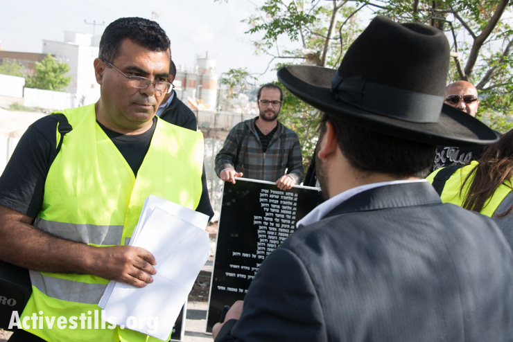 Umar Al-Ghubari of Zochrot is confronted by a Jewish passer-by as he leads the procession and reads the names of those killed in the massacre. (photo: Activestills.org)