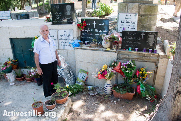 Hanna Nasser stands near his family graves in the cemetery of the displaced Palestinian village of Iqrit in northern Israel, April 21, 2014. Iqrit's original inhabitants were forcibly evacuated in the Nakba of 1948. Though the Israeli high court granted the residents, who are Palestinian citizens of Israel, the right to return to their homes in 1951, the military destroyed the village and has since prevented their return. Only the village's church and cemetery remained intact, and are still used by village residents while they campaign for a full return.