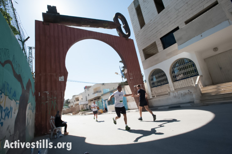 Palestinian and international runners exhange high-fives as they pass through the entrance of Aida Refugee Camp during the second annual Palestine Marathon in the West Bank town of Bethlehem, April 11, 2014. (photo: Activestills.org)