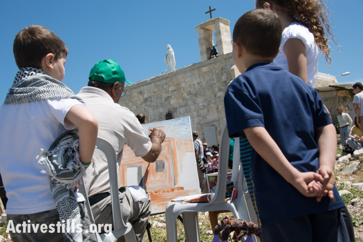 Children watch as an artist paints a picture of the church in the displaced Palestinian village of Iqrit in northern Israel, April 21, 2014. Iqrit's original inhabitants were forcibly evacuated in the Nakba of 1948. Though the Israeli high court granted the residents, who are Palestinian citizens of Israel, the right to return to their homes in 1951, the military destroyed the village and has since prevented their return. Only the village's church and cemetery remained intact, and are still used by village residents while they campaign for a full return.