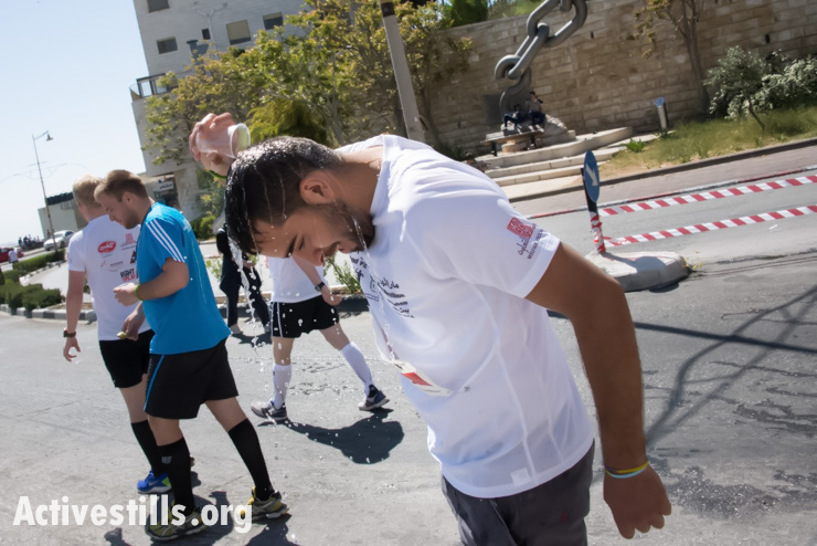 A runner pours water over his head at an aid station during the second annual Palestine Marathon in the West Bank town of Bethlehem, April 11, 2014. (photo: Activestills.org)