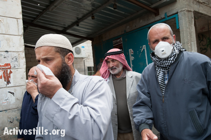 "Mourners in the funeral procession of Noha Katamish cover their faces from the effects of ""skunk water"" sprayed by Israeli forces in Aida Refugee Camp the previous day, West Bank, April 15, 2014. Noha Katamish, who had asthma, died from the effects of a tear gas grenade fired into her home by Israeli forces the previous day. She was the mother of one daughter. ""Skunk water"" is a foul-smelling liquid sprayed from a water canon as a crowd control weapon that leaves a weeks-long stench."