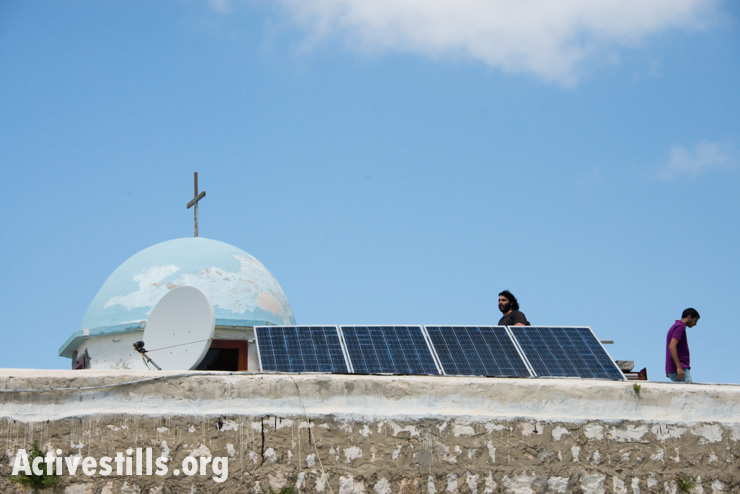 Solar panels and a satellite dish are installed on the roof of the church of the displaced Palestinian village of Iqrit in northern Israel, April 21, 2014. Iqrit's original inhabitants were forcibly evacuated in the Nakba of 1948. Though the Israeli high court granted the residents, who are Palestinian citizens of Israel, the right to return to their homes in 1951, the military destroyed the village and has since prevented their return. Only the village's church and cemetery remained intact, and are still used by village residents.